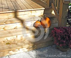 Pumpkins and a pot of mums decorate the steps of a wooden front porch.