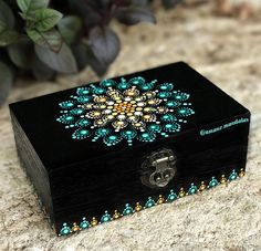 This is a wood box ( 15 cm x 10cm x 5,5 cm ) painted in black in the outside, and in orange in the inside. It has a handmade mandala design on the top. I used acrylic paint for the work, and i finished it with a spray of lacquer, to preserve it. The colors that i used have a spiritual meaning for me: Green: Nature, hope and stability Orange:Energy, balance Yellow: Joy, happiness I hope you like it as much as i do ❤