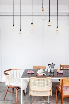 mismatched chairs around a rustic modern table with hanging exposed lights