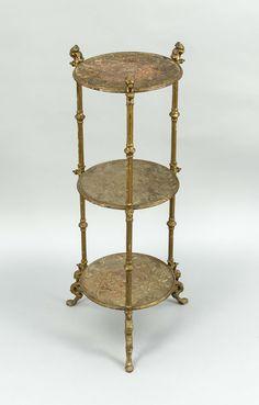 Eisenetagere um 1900, goldbronzierter Eisenguss mit drei runden, reliefierten Platten an drei Beinen mit Löwenköpfen und Greifen, ber. u. korrodiert, 78 x 29 cm