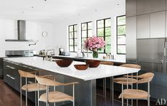 The bold, modern and striking kitchen (the cabinetry is by Bulthaup and really grounds the space beautifully), includes suede stools with a sculptural form and stainless frames.