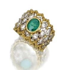 Buccellati 18 Karat Gold, Emerald and Diamond Ring. The oval emerald weighing approximately 1.00 carat, flanked by round diamonds, mounted in 18 karat yellow and white gold.