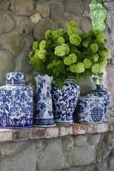 blue and white ginger jars and vases with Snowball Viburnum flowers-stone mantel/outdoor fireplace