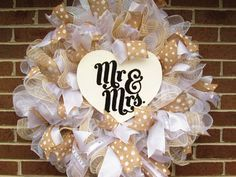Beautiful Wedding Wreath to celebrate your first day as Mr. and Mrs! This is a full wreath made using white deco mesh and filled in with white deco mesh and tan and white faux burlap mesh, accented with burlap polka dot ribbons, white sparkling ribbon and white sheer ribbon. In the center is a rustic wooden heart with Mr. and Mrs. hand stenciled in black paint. Would be beautiful on your church doors or at your reception site or rehearsal dinner! Perfect to help you celebrate your wedding…
