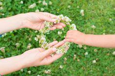花の冠を手渡す親子の手