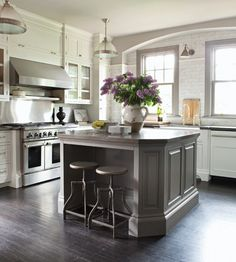 White Kitchen cabinets, beautiful gray island + arched soffit over window