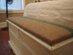 burlap covered cushion for love chest at the end of the bed.