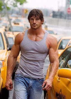 Hunky buffed male wearing gray tank top and showing off his nice BICEPS