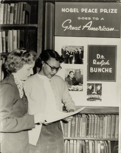 Women Reading - holdthisphoto: Two women stand in a library in...