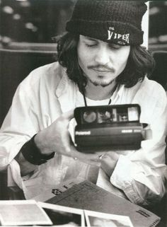 Johnny Depp rocking grunge, a Viper Room beanie and a Polaroid camera, peak 90s