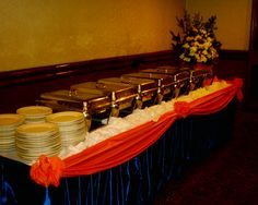 how to set up a buffet table   Buffet tables with motif skirting and floral arrangement