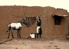 Banksy in Timbuktu- a woman hanging laundry on a line while a zebra stands by.