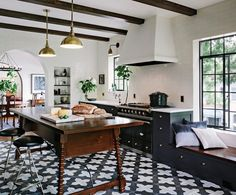 "Helgerson hewed to a black/white/brass palette in her design for the kitchen. The center island is custom, designed ""in a style reminiscent of a traditional Spanish table but higher for counter use,"" she says."