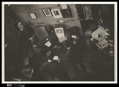 Man Ray's studio in Paris was a nerve center for avant-garde experimentation in the 1920s. Here a group of the artist's friends and collaborators watch a movie, probably one of Man Ray's own fanciful films, which is projected onto a white board propped against a camera case