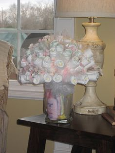 The diapers are rolled around wooden skewers and secured with clear rubber bands, and then pushed into a foam ball which is hidden and wedged into the vase. Accent with tulle. Isn't it pretty? I have such talented friends.
