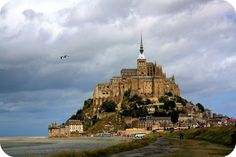 Mont Saint-Michel is located near the Normandy/Brittany border on France's northern coast about 150 miles almost due west from Paris. Despite that shortish distance, though, there is no public transport that runs directly to the site, so getting to Mont Saint-Michel can take several hours and is probably not an easy day-trip from the City of Light.  One option is to take a TGV train to the Pontorson-Mont St-Michel train station with a stopover in Rennes.