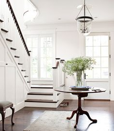 white and bright entry - like how the stairs have a landing in front of the windows
