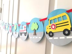This banner contains a police car, fire tuck, ambulance, and school bus with tree accents in between. It is a perfect banner for a little boys birthday party or a wall decoration! The banner is made with nine 6 blue circles with gray/white street design connected with red colored