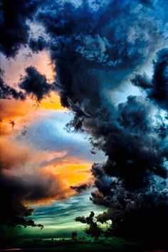 Storm clouds meet sunset over the ocean.
