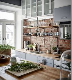 Vintage modern kitchen featuring exposed brick walls, open…