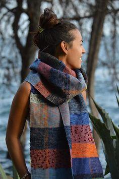 Deze kleurrijke handgeweven sjaal heeft 3D-textuur dankzij de vermenging van lokale dikke katoen en zachte wol. De draden zijn op het weefgetouw handmatig gedraaid en samengevoegd met de draden van gerecyclede truien.
