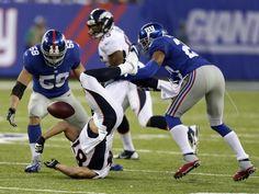 Eiserne Regel im American Football: Wer den Ball hat, der darf zu Boden geworfen werden.  Eric Decker (M) von den Denver Broncos wird durch Mark Herzlich (l) und Corey Webster von den New York Giants aufgehalten. (Foto: Jason Szenes/dpa)