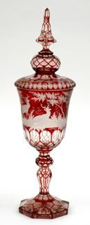 A fine Bohemian flashed ruby glass cup and cover, the ogee body finely carved with a scene showing deer in a forest setting, within thumbnail cut surrounds, the conforming cover terminating in a facetted finial   c. Late 19th Century