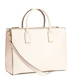 Handbag in thick, embossed imitation leather. Double handles and detachable shoulder strap at top, one large compartment, two zipped compartments on long sides, and three inner compartments, one with zip. Studs on base. Size 11 x 15 in.