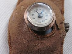 """An odd """"button watch"""" sewn into a leather band from the late 1910s-early 1920s."""