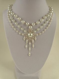 This beautiful and elegant necklace displays an array of shapes and sizes of white pearls with a central, chandelier style setting, for added richness and glamour. This fashionable necklace is made of white round glass pearls ( 4, 6 and 8mm) and white rice glass pearls, hand wrapped in non tarnish silver plated wire.The necklace measures 16 1/2 on the inner strand, and the central widest part is 3. To see a pair of matching earrings please follow the link…