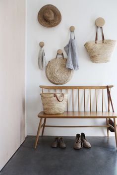 Natural tones in the baskets, wooden bench and pale terracotta plastered wall | Tessa Hop home entry