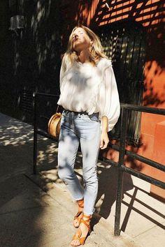Uma bata larguinha com calça jeans clara e bolsa de palha