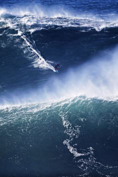 A surfer rides a big wave during a tow-in surfing session at the Praia do Norte or North beach, in Nazare, Portugal, Saturday, Nov. 29, 2014.