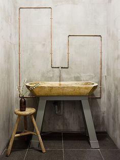 Love the industrial look with the copper pipes and walls, the wood sink offsets it with an organic touch.