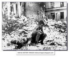 A forlorn Polish boy sits in the ruins of his house in Warsaw