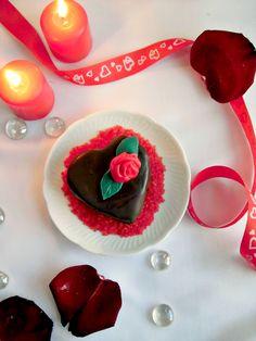 Le mini cakes al cioccolato a forma di cuore sono piccole tortine romantiche e golose. Un dolce al cioccolato, farcito con una cremosa ganache al cioccolato bianco e ricoperto da una glassa fondente, come decorazione una piccola rosa rossa in pasta di zucchero. Un delizioso dessert con tutti gli elementi essenziali per festeggiare San Valentino.
