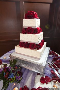White three-tier square cake with swirled piping and red rose accents on each tier and silver ribbon | villasiena.cc