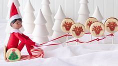 The Elf on the Shelf® takes a ride through the snow, pulled on a sleigh  by reindeer cookie pops!