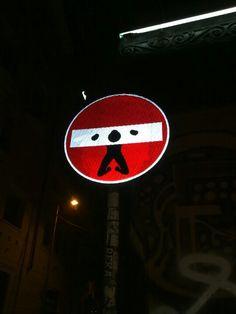 Man on the guillotine/no access sign (near Duomo)
