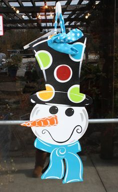 "You can keep ol' Frosty on your front door all winter long!  This 14""x32"" snowman is made using 1/4"" wood, sanded, finished, and hand painted.  UV protected for exterior use.  Features a wintery blue scarf and polka dot top hat. Oh, and we cant forget his carrot nose and two eyes made out of coal!"