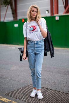 Street style: camiseta oversized com o jeans de cintura alta é super cool, ainda mais com uma jaqueta jeans escura e tênis branco.