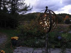 "Another way to use the whiskey barrel rings & incorporate some of our grape vines - ""We made an orb with two rusted steel bands from an old whiskey barrel planter. They're held together at the top with a rusted-iron hose guide, which fits into a metal pipe that anchors the whole thing to a cedar post. Around the center of the pipe I wove a loose ball of wild grape vines. Then I stuffed the ball with a 24-foot string of LED lights."""