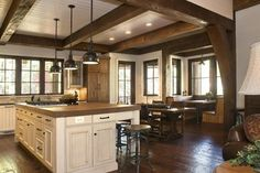 Love the colour of the floors with the matching beams. Distressed wood floors made of pine and stained.   Rustic Lakehouse - kitchen - other metro - Wright Design