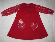 Robe pure flanelle de coton rouge pur coton motifs poupées russe. Toute douce, voici une robe à manches longues resserrées au poignet par un élastique. Les manches sont en pur coton rouge au motifs de petites poupées russes multicolores. Deux poches en forme de cœur sont plaquées sur le devant. Une poupée russe cousue en appliqué semble vouloir sortir de la poche droite. Six petits boutons boule entourent l'encolure avec fente. Cette robe conviendra très bien pour finir l'hiver ou au…
