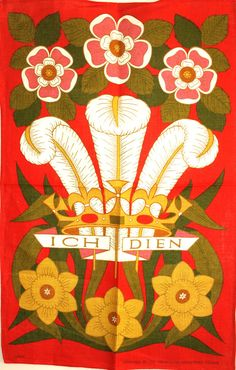 """Bold mid-century florals against a deep orange-red background surround the center Ich Dien feathered crest of this new old stock tea towel. The crest is the traditional Prince of Wales motto, meaning """"I Serve""""."""
