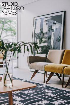 Nesse projeto assinado pelo Studio Leandro Neves, nós adoramos a elegância proporcionada pelo contraste entre o amarelo do sofá Chica, assinado pelo designer Zanine Caldas, e o preto e branco presentes no tapete e no quadro do arquiteto Leandro Neves! Foto: Alessandro Giraldi