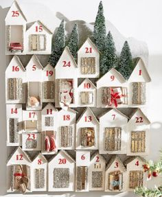 Lit from within, the windows of the Glitter Houses Advent Calendar glow in a wintry scene. Every member of the family will love opening the doors of this holiday village in a countdown to Christmas day. #xmas #christmas #adventcalendar
