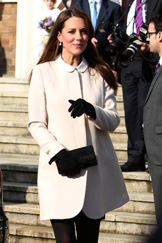 Kate wearing small drop earrings, black gloves, and a black clutch.