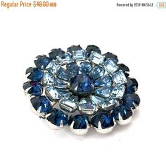 Brooch Sale     Kramer Shades of Blue Rhinestone Brooch  Measures: Approx. 2  Mark: Kramer  Condition: Beautiful vintage condition a small bit of speckling on back plating done @ manufacture  Talk about stunning this brooch is so beautiful!  - The three shades of blue rhinestone are just lovely together  - The radial shape is enhanced and made so much more interesting a  by the layering of tiers that create a wonderful concave effect  - Additional interest is created by the use of various…