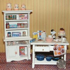 Dollhouse Miniature in one inch scale by DollysGallery.com Baking Table and Hutch Set includes ceramic cannister set, groceries and dishes, foil wrap, cooking pots, mixer, cake & stand, cupcakes, eclairs, measuring spoons, cup of coffee, forks in drawer, towel, bowl of icing & more.  This is in 1:12 scale, one inch scale.    All drawers and doors open & close.  Wonderful detail! Find DollysGallery also on ebay & FB. Check them out!